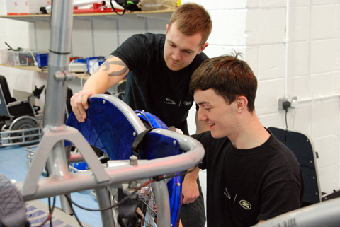 Apprentices from Jaguar with a Power Hockey Chair