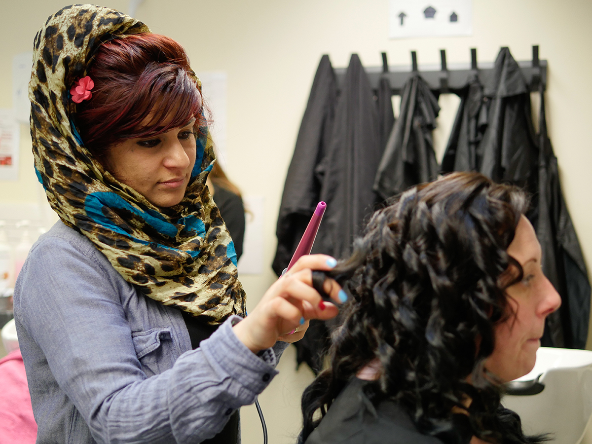 Hairdressing student using the curling wand on a client