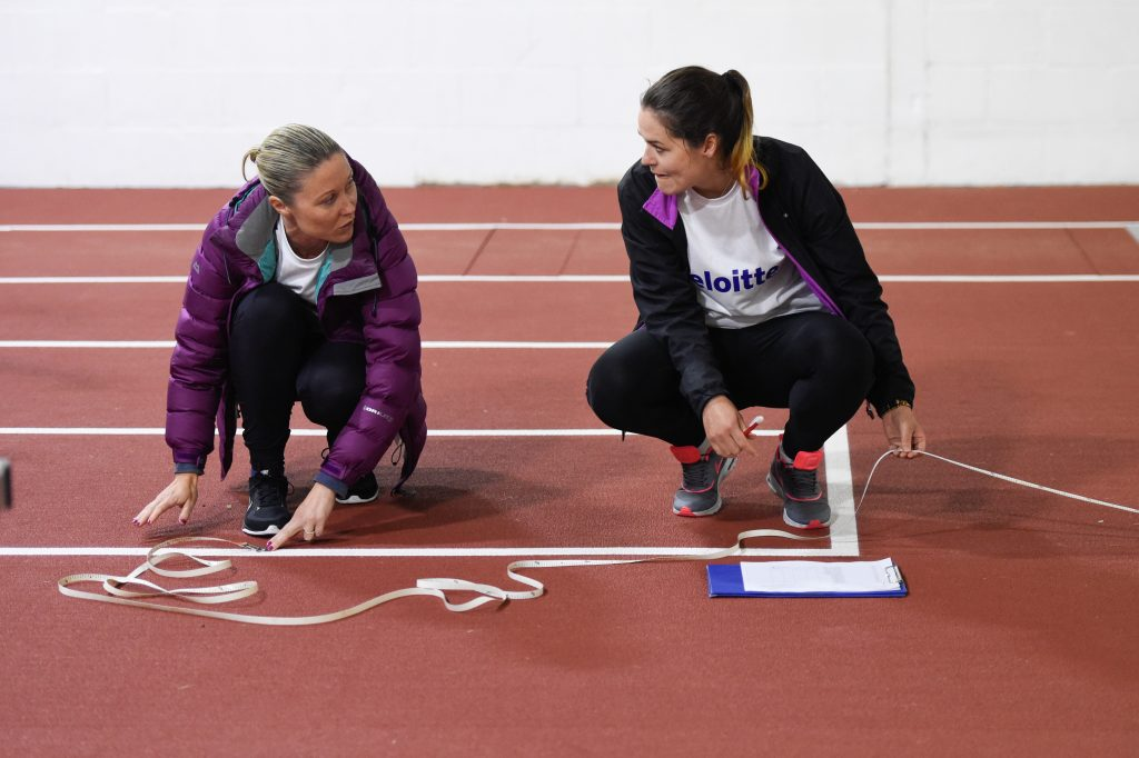 Volunteers from Deloitte measure javelin distance