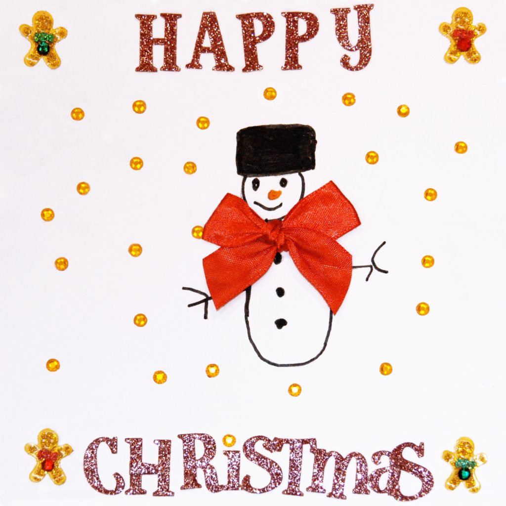 Handrawn snowman with a big red bow in the middle of a card saying Happy Christmas