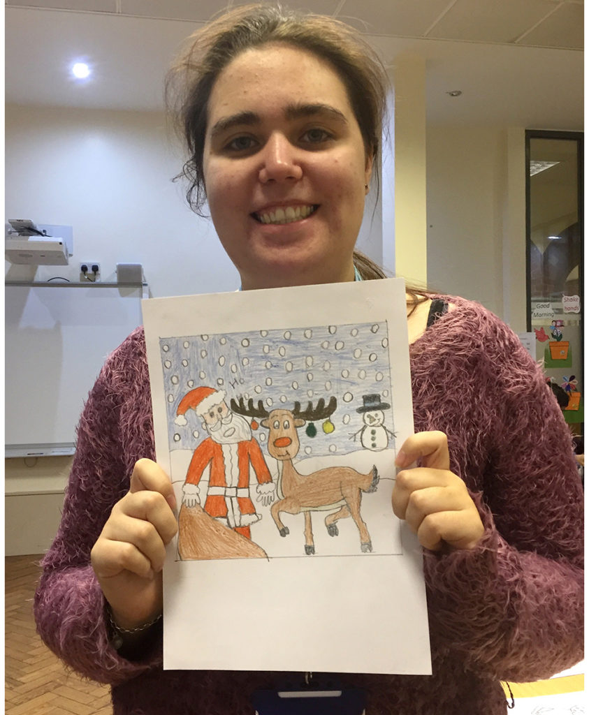 A student with their winning Christmas Card design.